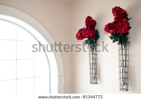 Red Flowers Aglow From Adjacent Glass Block Window - stock photo