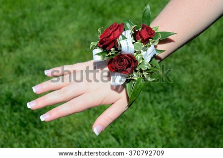 Red Flowers (Roses) on Wrist Corsage for Prom - stock photo
