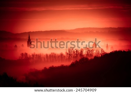 Red foggy dawn in town of Krizevci, church towers in fog, Prigorje region of Croatia - stock photo
