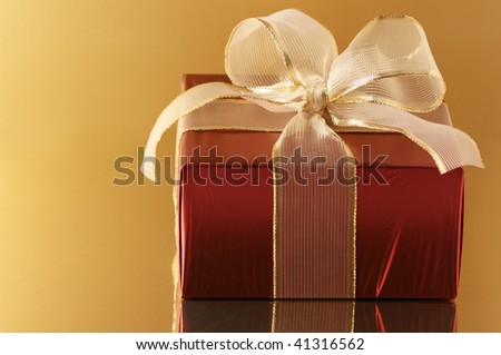 Red foil gift with gold translucent bow on golden background. - stock photo