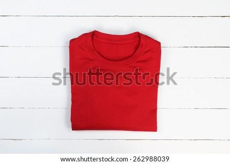 Red folded t-shirt on white wooden background. Tshirt mockup - stock photo