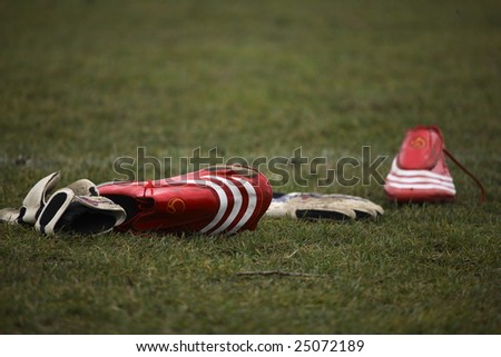 Red Football Shoes And Gloves On A Field - stock photo