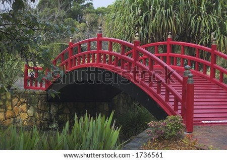 Red footbridge over a stream flowing through a Japanese garden - stock photo