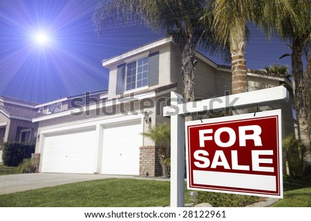 Red For Sale Real Estate Sign in Front of House with Blue Starburst in Sky. - stock photo