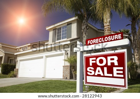 Red Foreclosure For Sale Real Estate Sign in Front of House with Red Star-burst in Sky. - stock photo