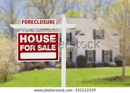 Red Foreclosure Home For Sale Real Estate Sign in Front of House. - stock photo