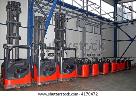 Red fork lifter trucks and carriers in warehouse - stock photo