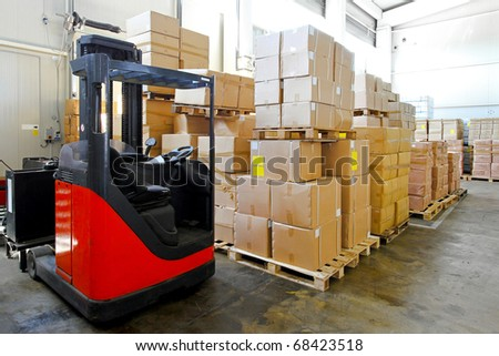 Red forklift in big warehouse with boxes - stock photo