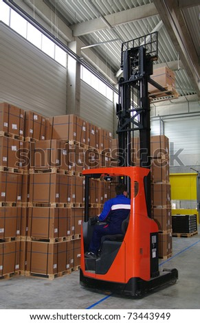 Red forklifter work in big warehouse - stock photo