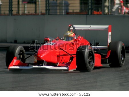 Red formula racing car coming through a street circuit corner