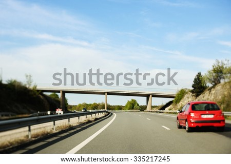 Red french car on typical French highway - tilt-shift lens used - stock photo