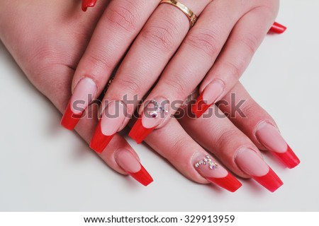 Red french nail art with rhinestones on white background