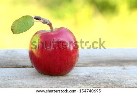 Red, fresh and organic apple on wooden table
