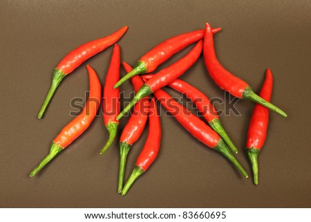 Red, fresh cayenne peppers. Vegetables on brown background.