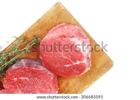 red fresh fillet chops : three raw beef fillet chops on wooden board with thyme twig ready to prepare . isolated over white background - stock photo