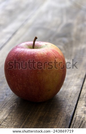 Red fresh organic apple on  old wooden table, backlit - stock photo
