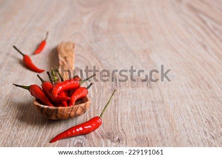 Red fresh pepper on a wooden surface - stock photo
