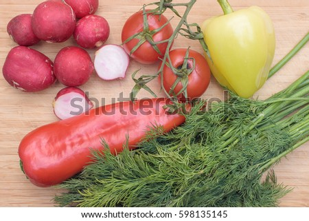 Red fresh radish, tomato, green and red pepper and green dill on wooden kitchen board Top View
