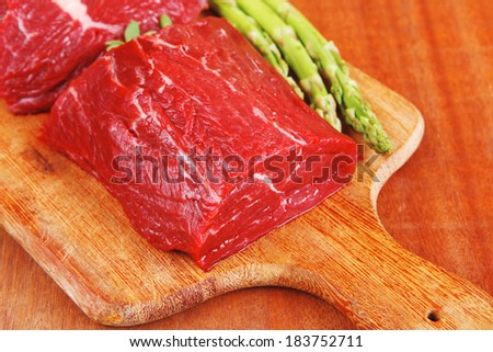 red fresh raw beef veal fillet with asparagus on cutting plate over wooden table prepared to use - stock photo