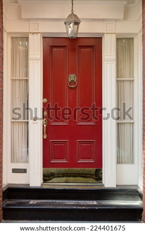 Red Front Door with Surrounding White Door Frame and Windows and Overhead Hanging Lamp - stock photo