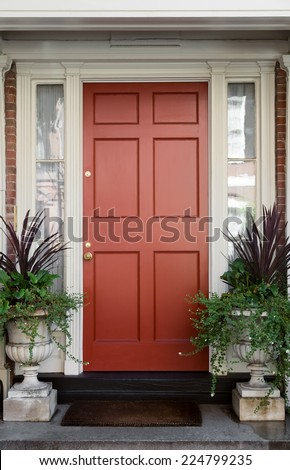 Red Front Door with Surrounding White Door Frame and Windows and Potted Plants - stock photo