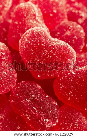 Red fruit candy in the form of the heart, strewed by sugar - stock photo