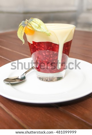Red fruit slightly stewed and thickened with vanilla sauce, served in glass dish on white plate; Typical German dessert; Sweet fruit dish