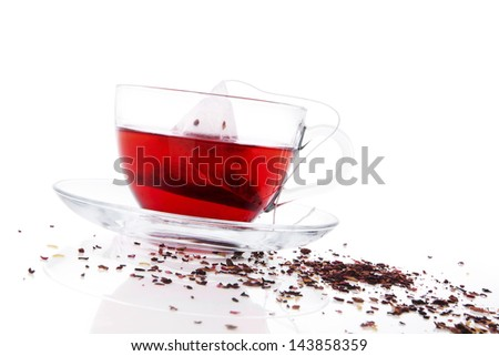 Red fruit tea in transparent tea cup with tea bag. Dried tea in background. Healthy winter drink concept.