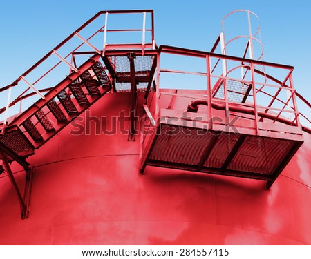 red fuel tank with a stairs on the wall - stock photo