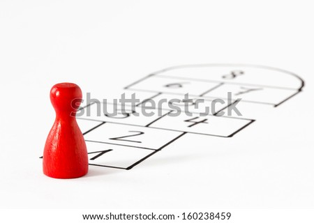 Red Game figurine before a hopscotch layout