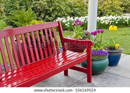Red Garden Bench On Patio Surrounded By Pots Of Colorful Spring Flowers