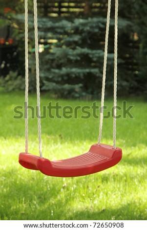 Red garden swing hanging in garden - stock photo