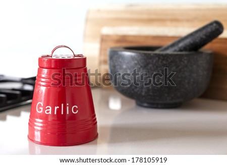 Red garlic storage container on kitchen bench - stock photo