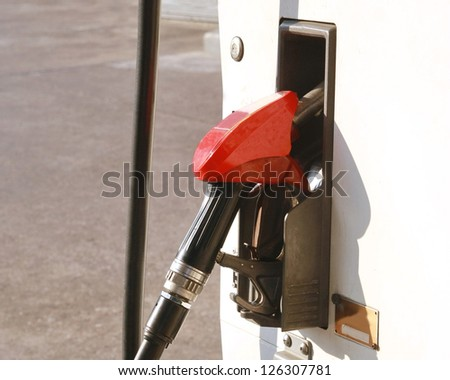 red gas pump nozzle ,close-up of refilling the car with a gas pump, energy and clean fuel background