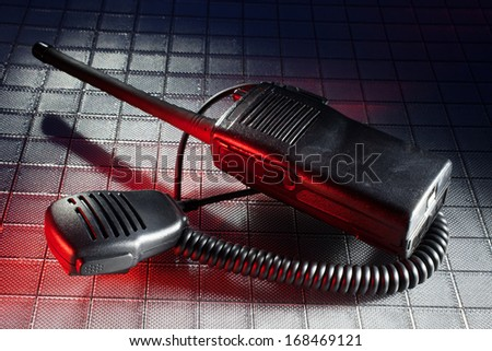 Red gel from the right on a two way radio and microphone - stock photo
