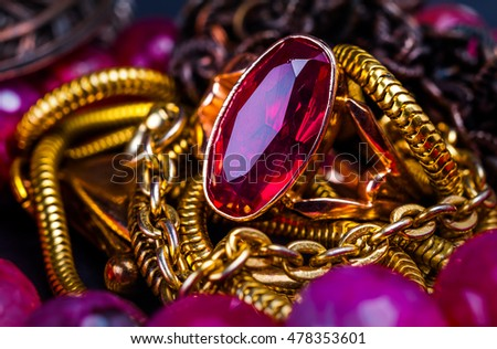Red gem in a rim on the background of the jewelry chains close-up