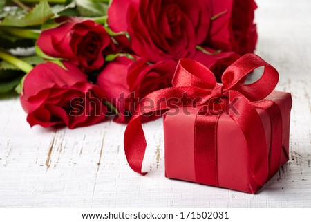 Red gift box and bouquet of roses on white wooden background - stock photo