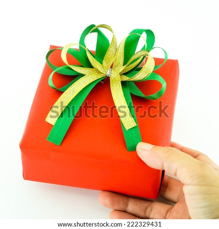Red gift box and green, gold ribbon bow in hand isolated on white background - stock photo