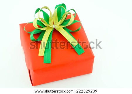 Red gift box and green , gold ribbon bow isolated on white background - stock photo