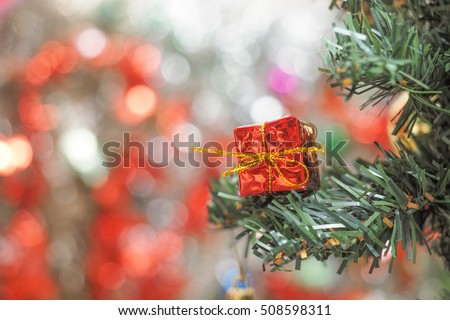Red gift box christmas ornaments on tree with color lights at the background
