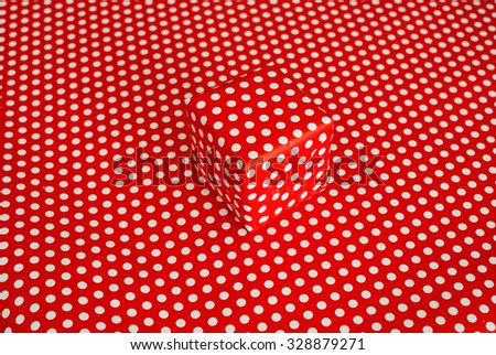 Red gift box isolated on red background with white dots - stock photo