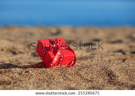 Red gift box on a beach - stock photo