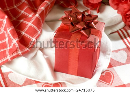 Red gift box on a table-cloth on red hearts
