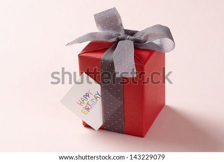 red gift box on pink background. red Gift box with gray ribbon.