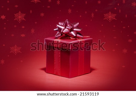 Red gift box on red background with snowfall - stock photo