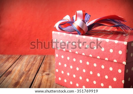 Red gift box on wood table and red
