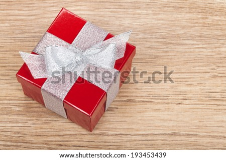 Red gift box on wooden table background. View from above with copy space