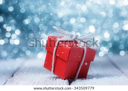 Red gift box over defocused lights - stock photo