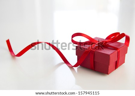 red gift box over white table - stock photo