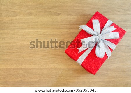 red gift box with a silver ribbon bow on wooden table, free space for text